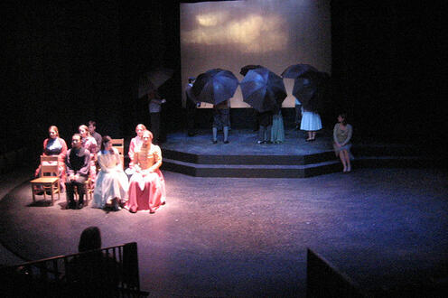 Group of people sitting on stage with another group in the background holding umbrellas