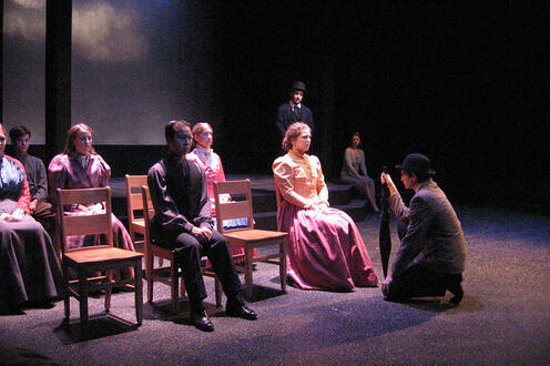 Group of people sitting on stage facing a man kneeling with an umbrella