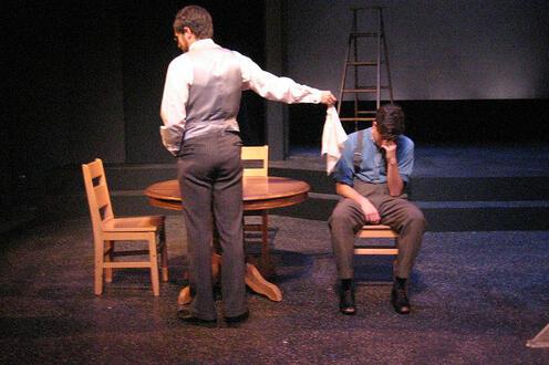 Man handing a handkerchief to another man in distress