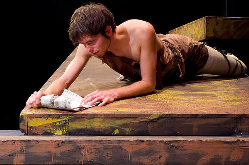 Man laying down and reading a scroll in the play 'Julius Caesar