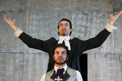 Man standing behind another man with his hands in the air