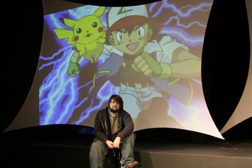 Boy sitting with Pokemon on screen behind him