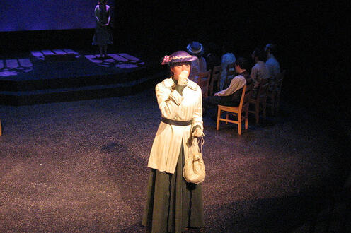 Woman standing on the stage with a group sitting in the background