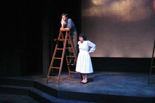 Man on a ladder on stage with a woman