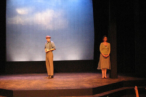 Man looking over his shoulder at a woman on stage