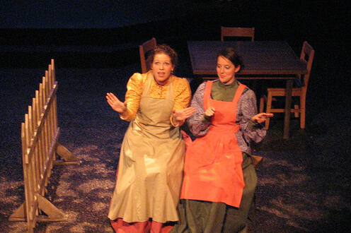 Two women sitting on stage in dresses