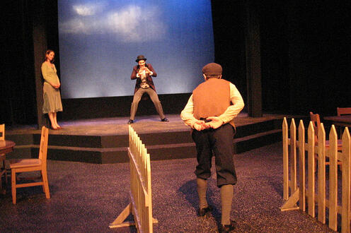 Two men face-off on stage while a woman looks on