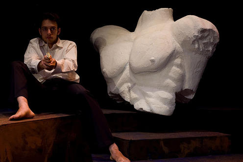 Man sitting and holding a knife in the play 'Julius Caesar'