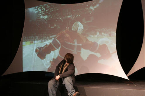 Boy sitting with hockey on screen behind him