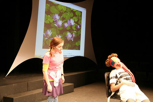 Girl looking at another girl with a clown nose in the play Alice (Experiments) In Wonderland