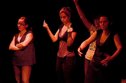 Girl holding up her middle fingers with others standing be her side in the play Differ/End: The Caledonia Project