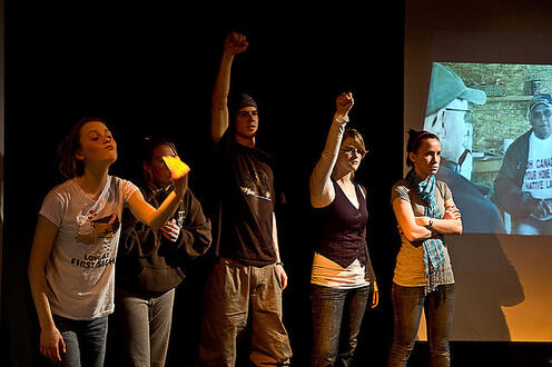 Five people standing and raising their fists in the play Differ/End: The Caledonia Project
