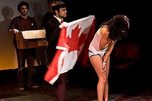 Girl in underwear being covered with a Canadian flag in the play Differ/End: The Caledonia Project