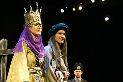 Woman standing wearing a crown with two men looking on