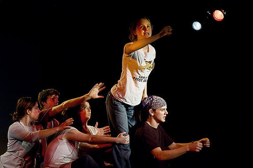 Girl standing above a group and holding out her hand