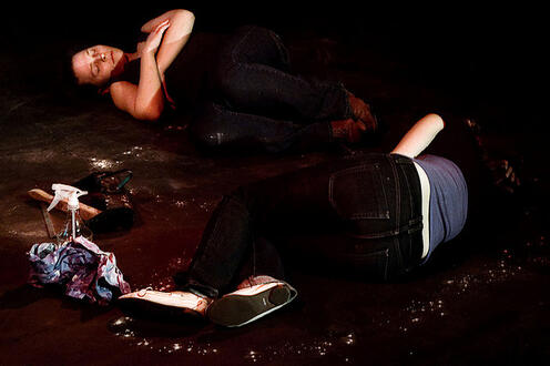 Two people on the ground pretending to be dead in the play Differ/End: The Caledonia Project