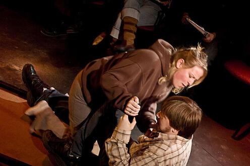 Girl straddling and grasping a man
