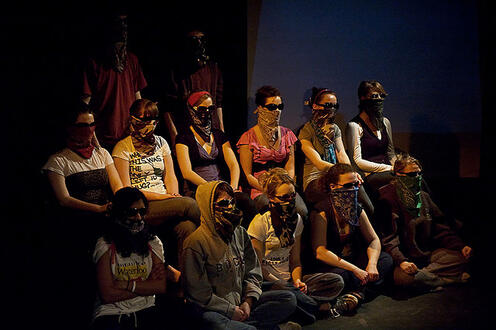 Group of people sitting with sunglasses and bandannas covering their faces