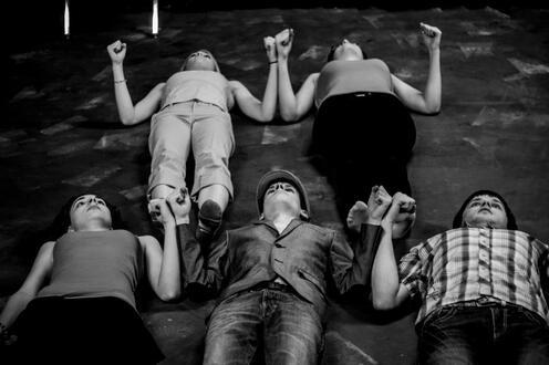 Actors hold hands on the floor