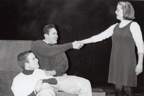 Man shaking the hand of a woman while another man looks on from his knees