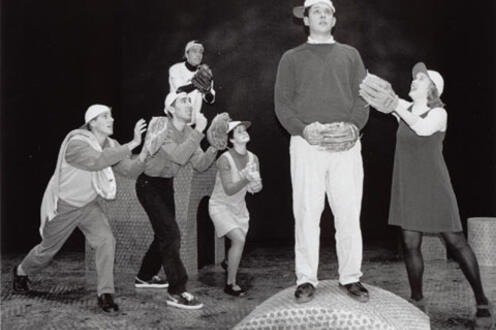 Man in foreground with a woman standing to his right, and four others looking at him in the background while they all wear baseb
