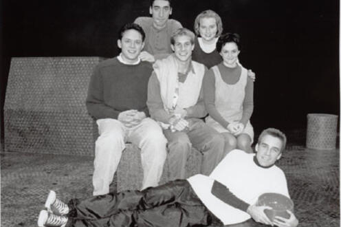 Cast of You're a Good Man Charlie Brown posing for a photo while one lies on his side in front of them