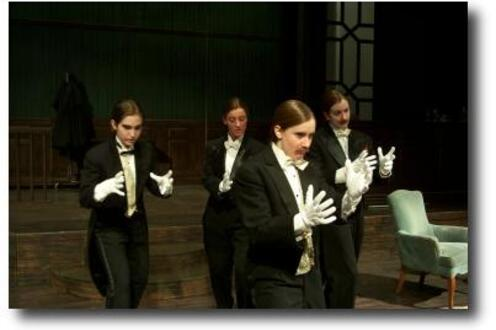 Group of people dressed in tuxedos holding out their hands as if grabbing something