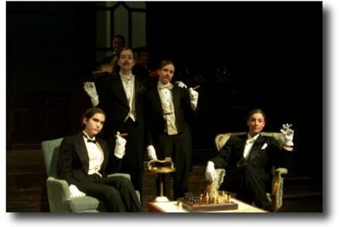 Cast of The Club dressed in tuxedos lounging around a chess board