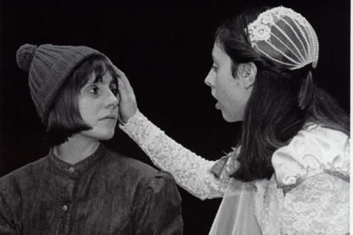 Woman in costume touching the face of another woman