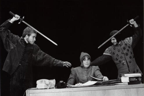Two men threatening a woman with swords from left and right, while she holds papers