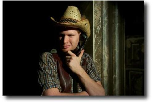 Man in a cowboy hat holding a phone to is ear