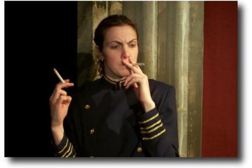 Woman smoking a cigarette with her left hand and holding another cigarette in her right hand