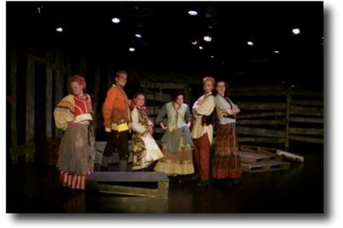 Four women and two men from the cast of Grimm Tales performing on stage