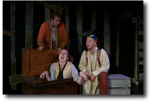 A woman being revealed from a box with two men looking on by her side