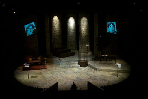 Picture of the stage for Gross Indecency with two faces being shown on screens