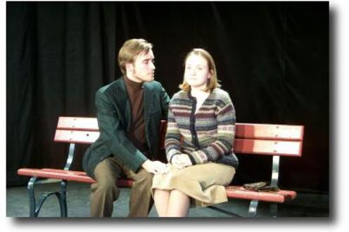 Man looking at a woman and sitting next to her on a bench
