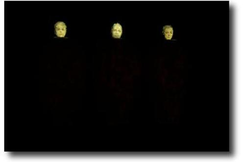 Three men with light illuminating their faces in a dark background