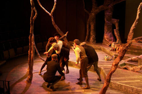 A person carrying another on their back while surrounded by four men on a forest-themed stage