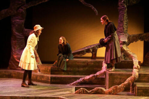 Three women walking to each other on a forest-themed stage