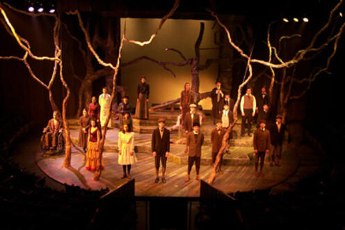 Cast of Spring Awakening standing on stage facing the crowd