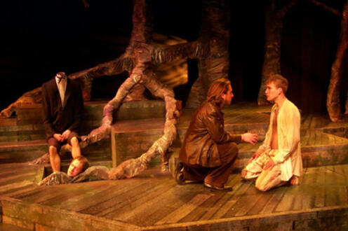 Two men talking to each other on their knees on forest-themed stage