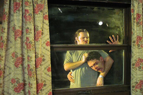 Man choking another man and rubbing his head while outside of a window