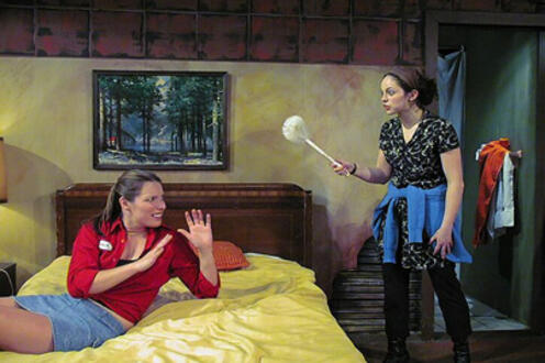 Woman threatening another woman on a bed with a dust brush