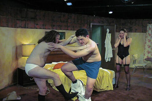 Two men in their underwear fighting while holding each other's shoulders