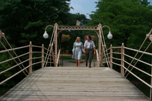 Man and woman holding hands walking on a bridge