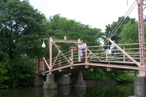 Man and woman standing on a bridge looking into the water