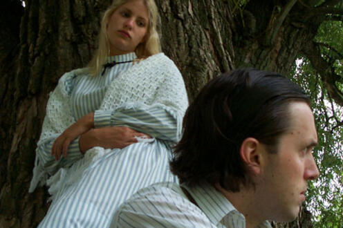 Woman leaning against a tree looking at a man