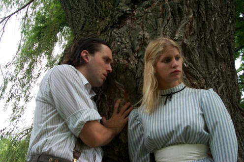 Man looking at a woman leaning against a tree