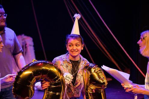 An actor is standing on stage with a birthday hat and big balloons that say 21