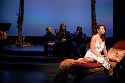 All Art Is Quite Useless - An actor is sitting on a fainting couch. Three actors can be seen behind the first actor.